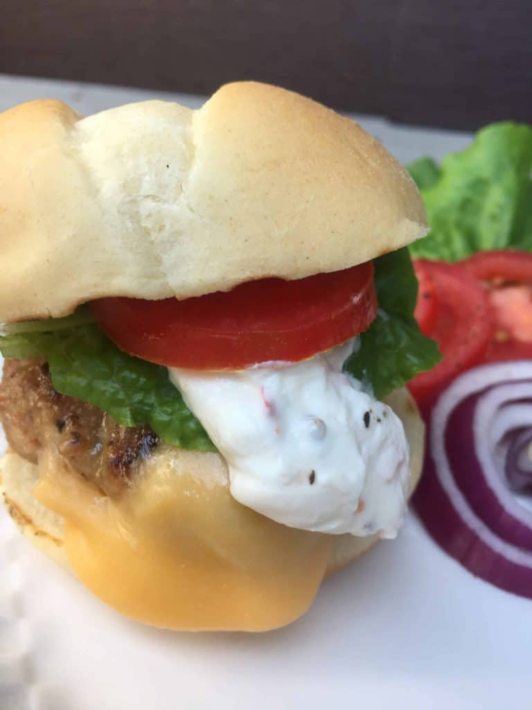 Turkey Slider with tomato and jalapeno cream, onions, lettuce in the background from Gourmet Done Skinny.