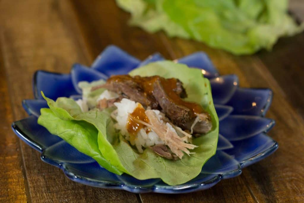Lettuce wraps with Kalua Pork on a blue lotus plate