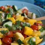 Colorful Mango Salsa in a blue bowl with wooden spoon