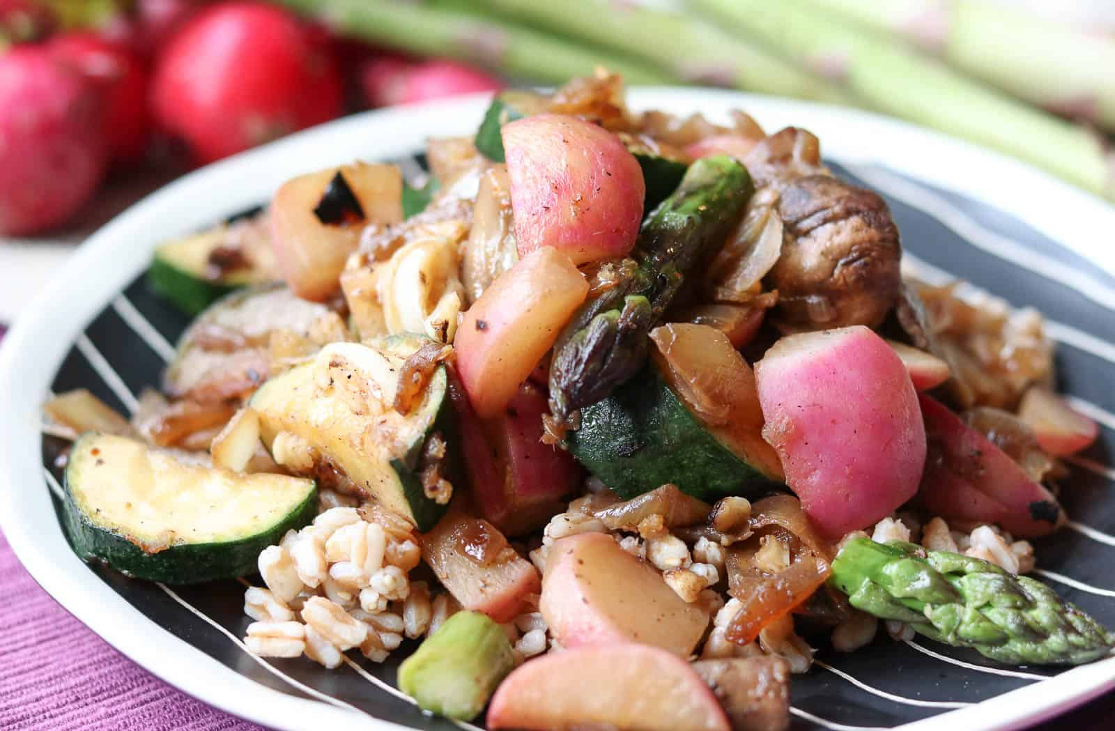 Asian Sautéed Radish Salad with Farro - Sauteed radishes, asparagus, mushrooms on top of farro on a plate