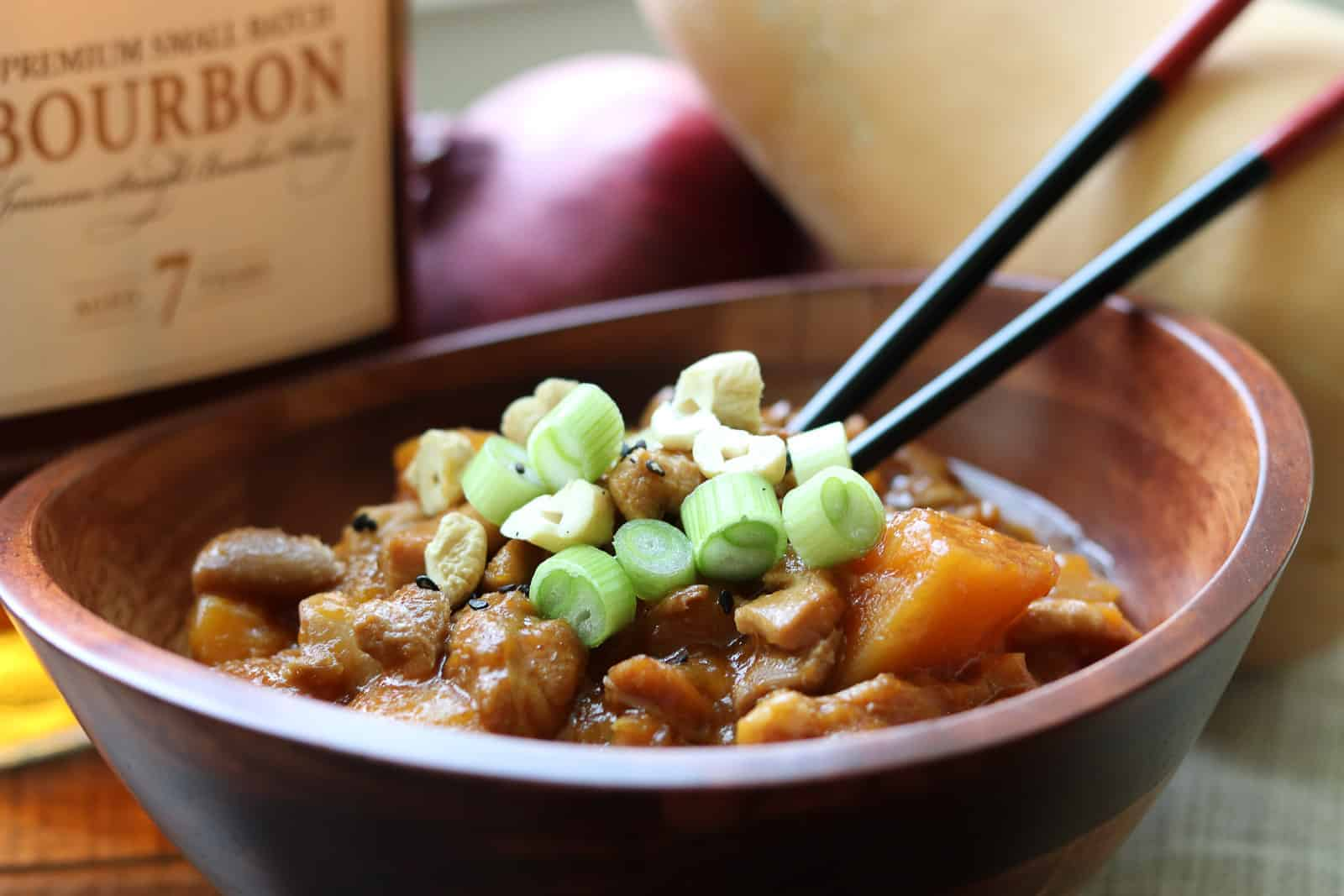 Instant Pot Bourbon Butternut Chicken from Gourmet Done Skinny in a wooden bowl with chopsticks, bourbon, butternut squash and onion on board nearby