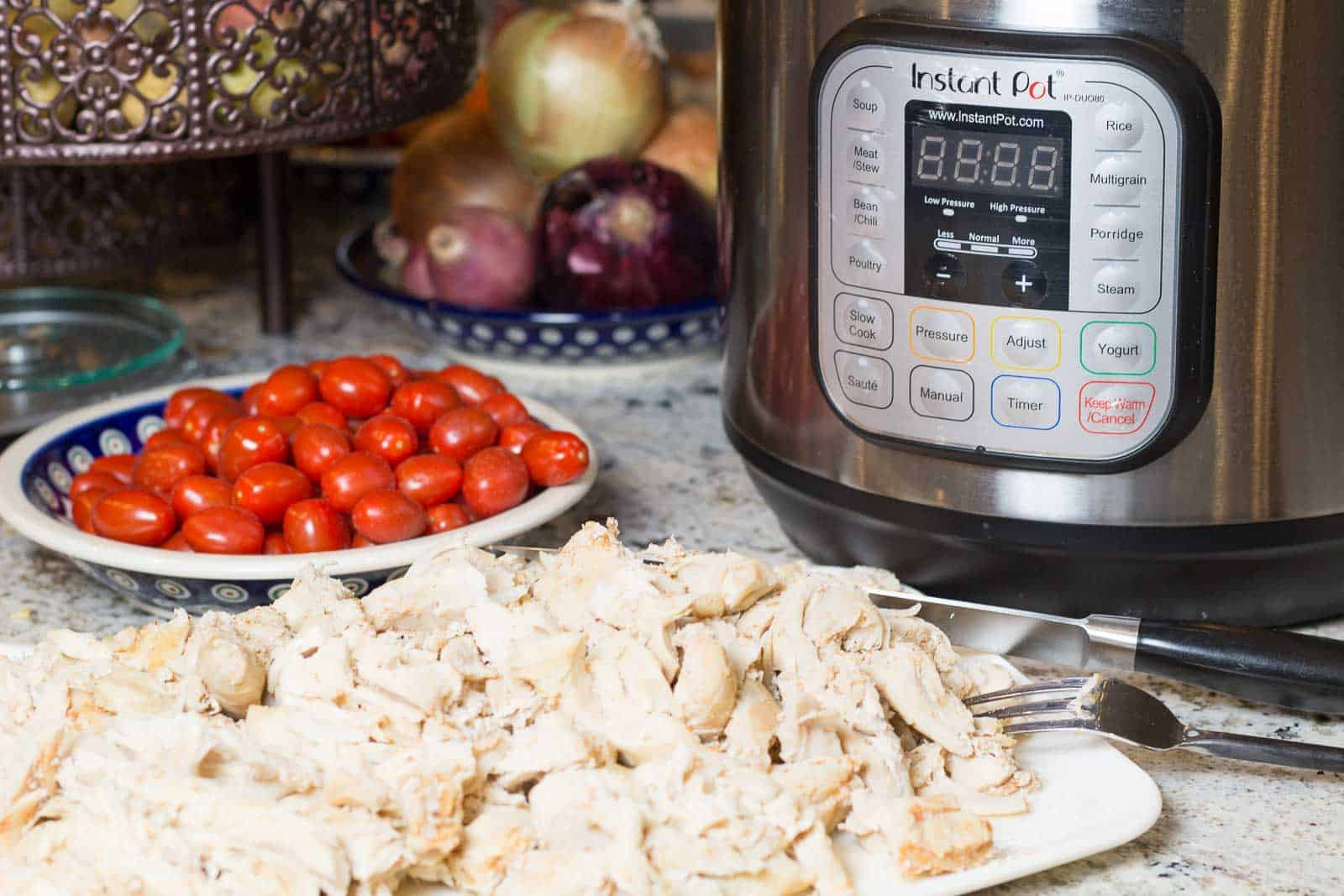 Instant Pot Shredded and Brined Chicken on a plate with Instant Pot and tomatoes and onions in background