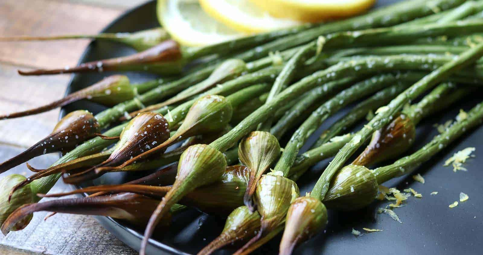 Air Fried Garlic Scapes on a black plate with lemon and lemon zest