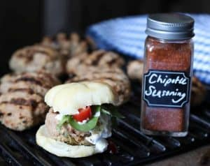 Spicy Jalapeño Adobo Turkey Slider on a grill with Chipotle Seasoning in a glass jar