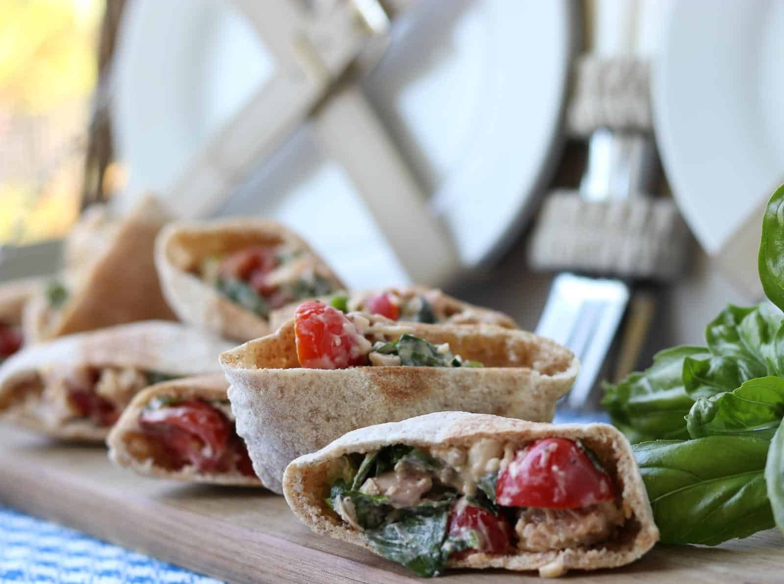 Mini Chicken Basil Parmesan Pitas on a wooden board with basil and picnic basket
