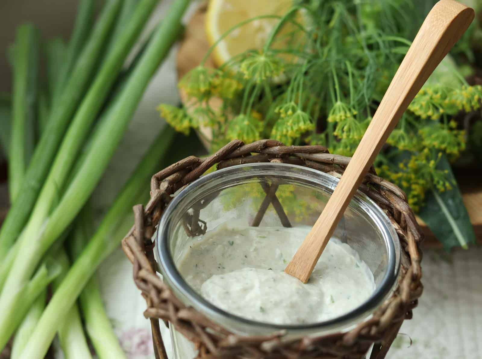 Healthy Garlic Ranch Dressing in a glass jar with wicker basket, green onions, dill and lemon on a fabric cloth