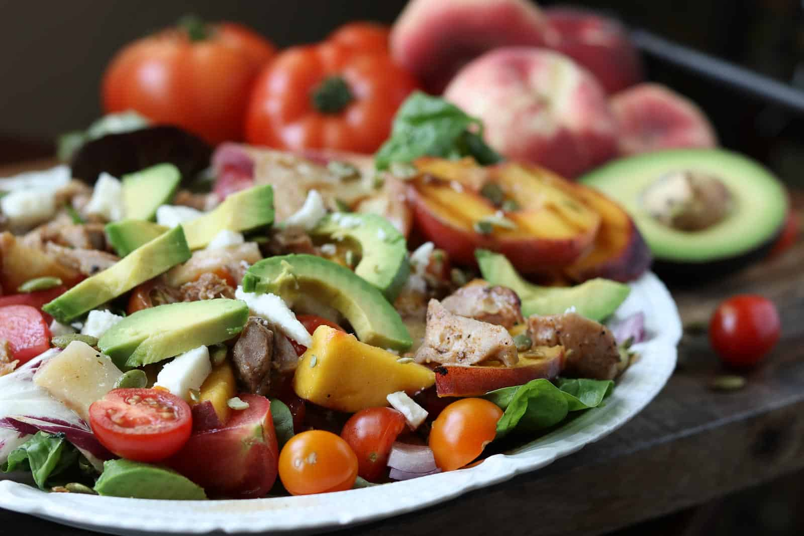 Summer Chicken Salad with fresh tomatoes, grilled peaches, avocados, pumpkin seeds on a white plate with tomatoes, peaches, avocados in the background