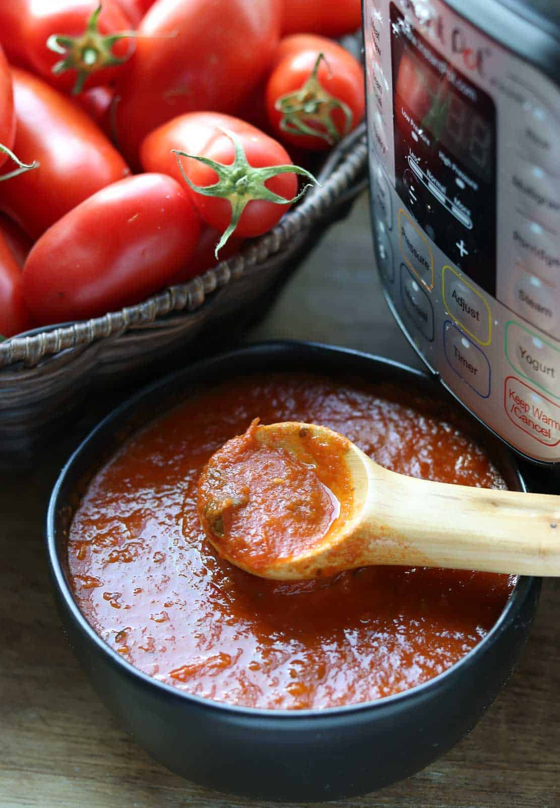 Instant Pot Homemade Tomato Sauce in a black bowl with Instant Pot and basket of tomatoes in background