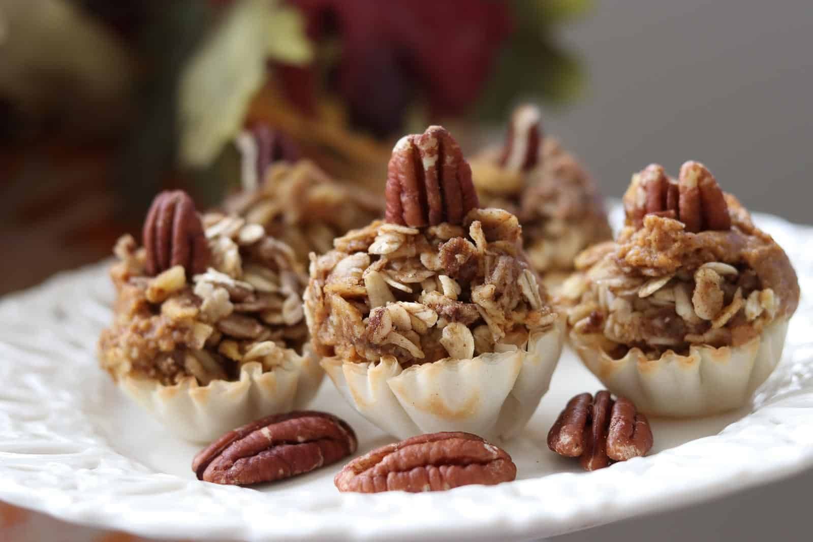 Easy Healthy Mini Pumpkin Pies with Cinnamon Cardamom Streusel on a cream plate with pecans.