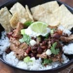 Quick and Easy Healthy Cilantro Pork Pot in a black bowl with rice, lime and tortilla chips