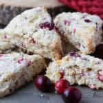 Delicious moist healthy homemade cranberry orange scones on a grey slate with fresh cranberries