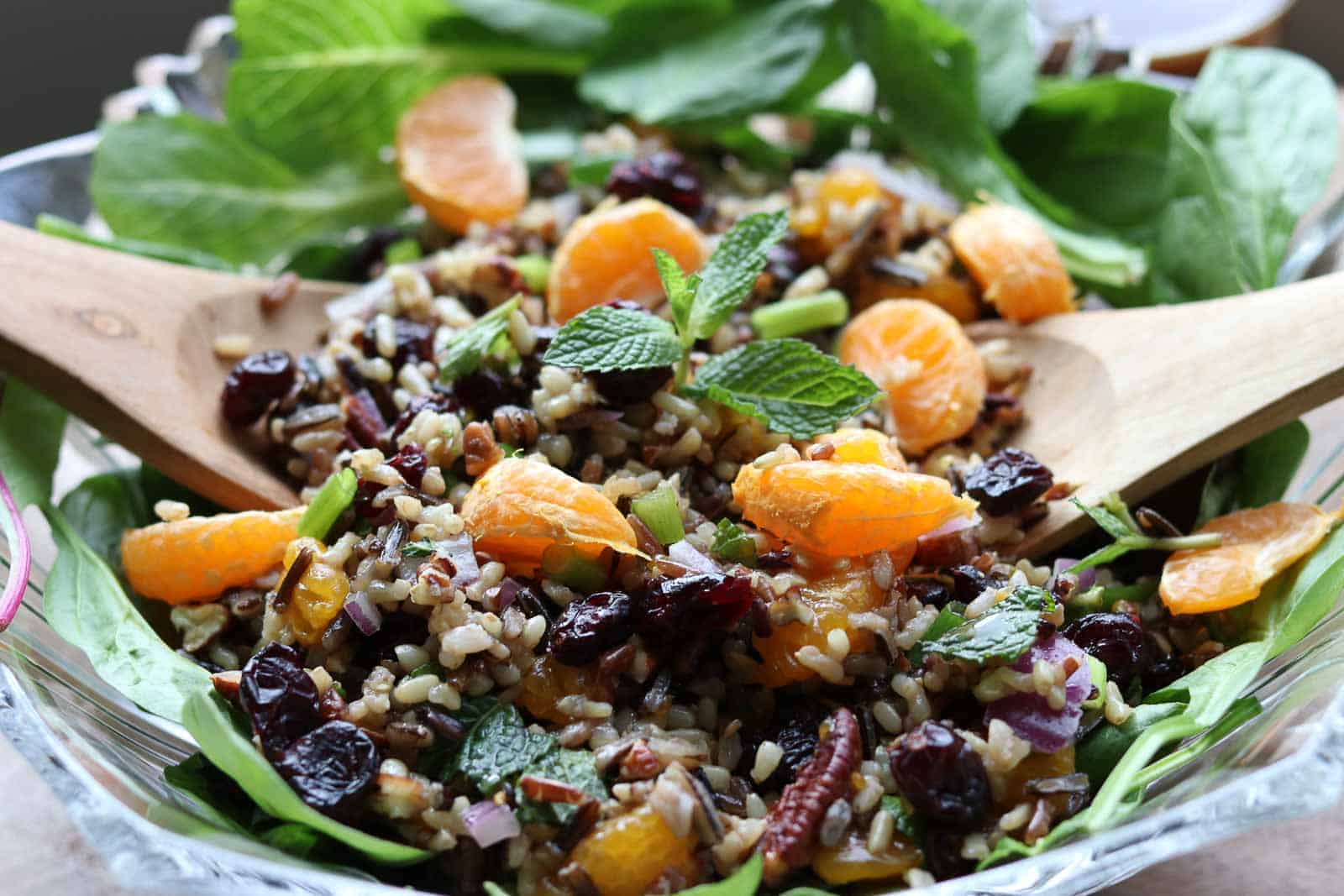 Mandarin Wild Rice Salad is a hearty autumn salad with cranberries, pecans, green onions, chopped mint and mandarins with a delightful orange vinaigrette in a glass bowl from Gourmet Done Skinny