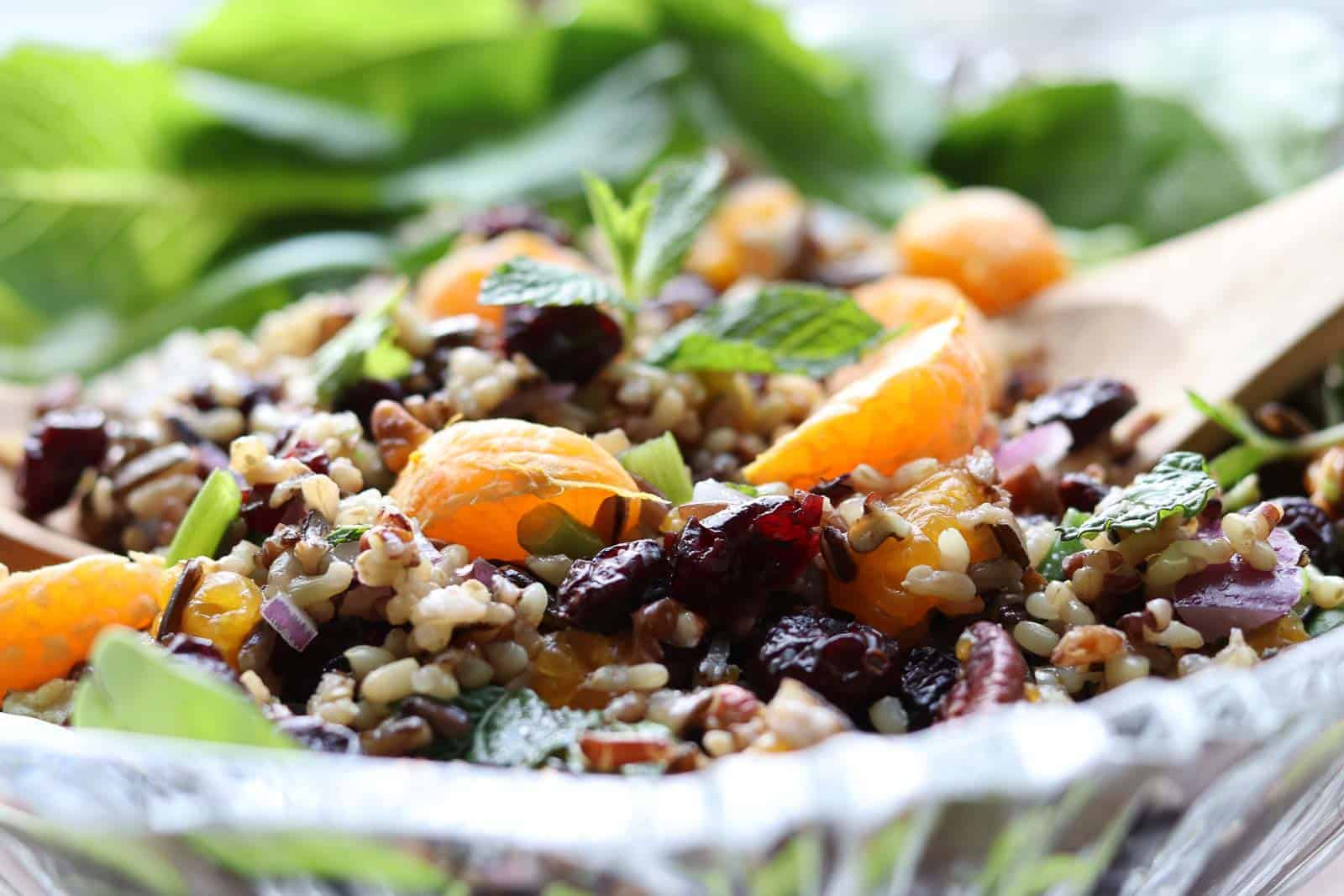 Mandarin Wild Rice Salad with Cranberries, Mint and Pecans in a glass bowl with a wooden spoon from Gourmet Done Skinny