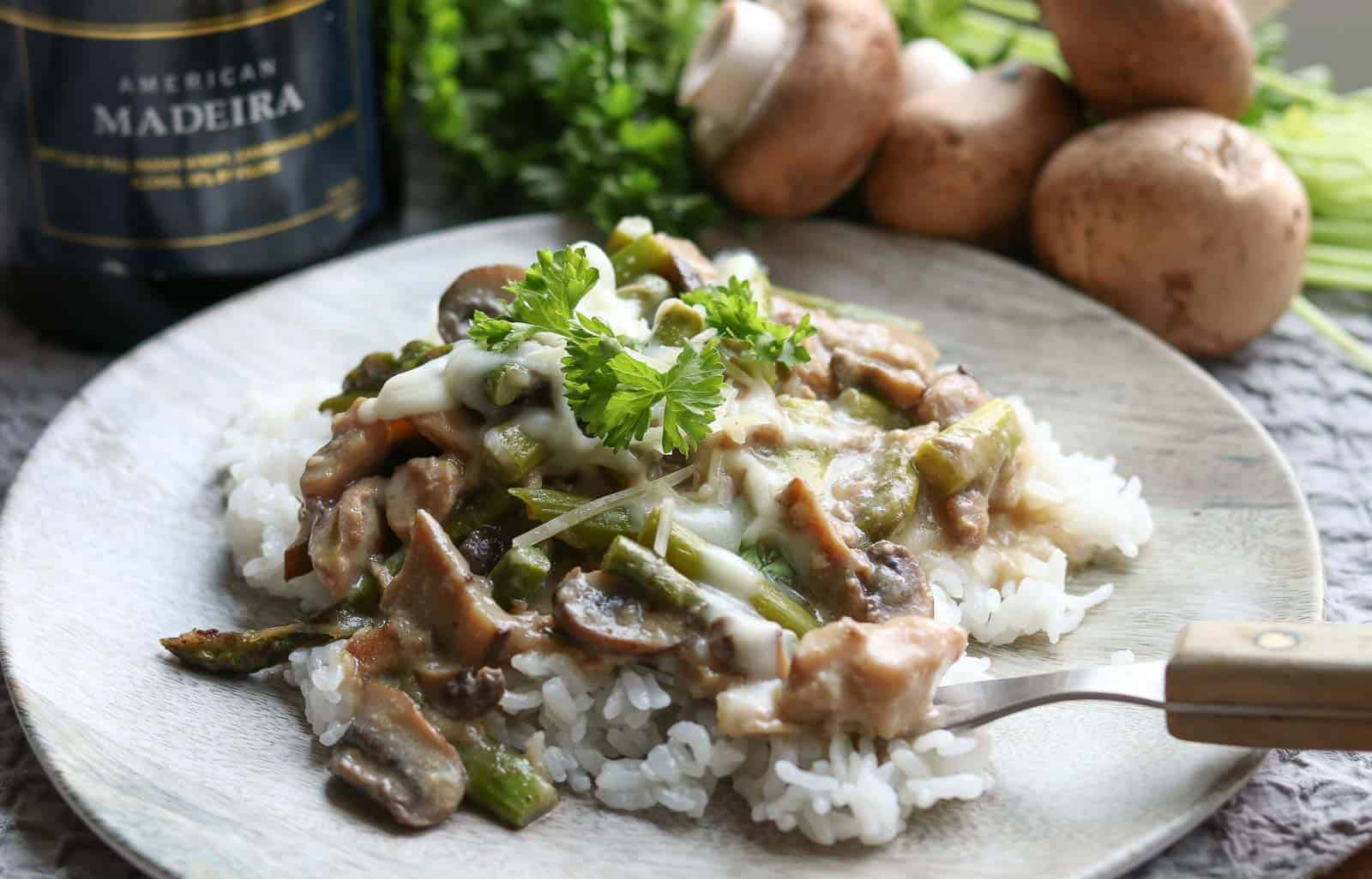 Easy Healthy Instant Pot Chicken Madeira on a wood plate with mushrooms, parsley and Madeira wine in the background from Gourmet Done Skinny