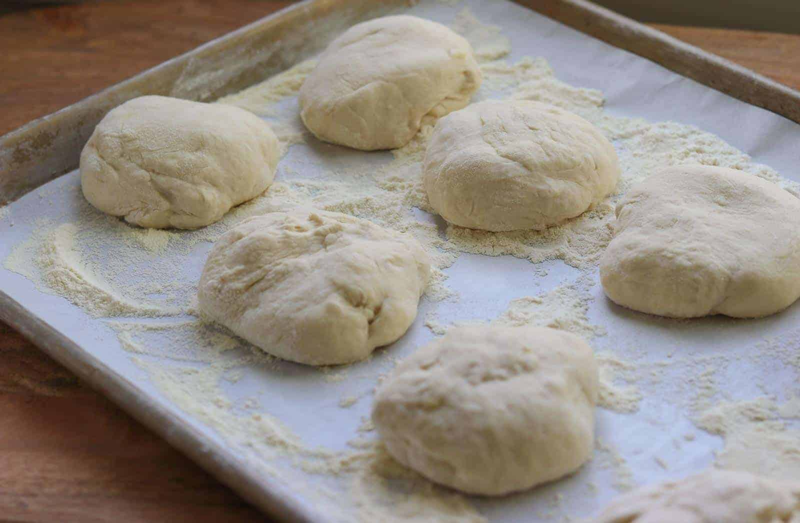 Pizza dough on a baking sheet lined with parchment from Gourmet Done Skinny
