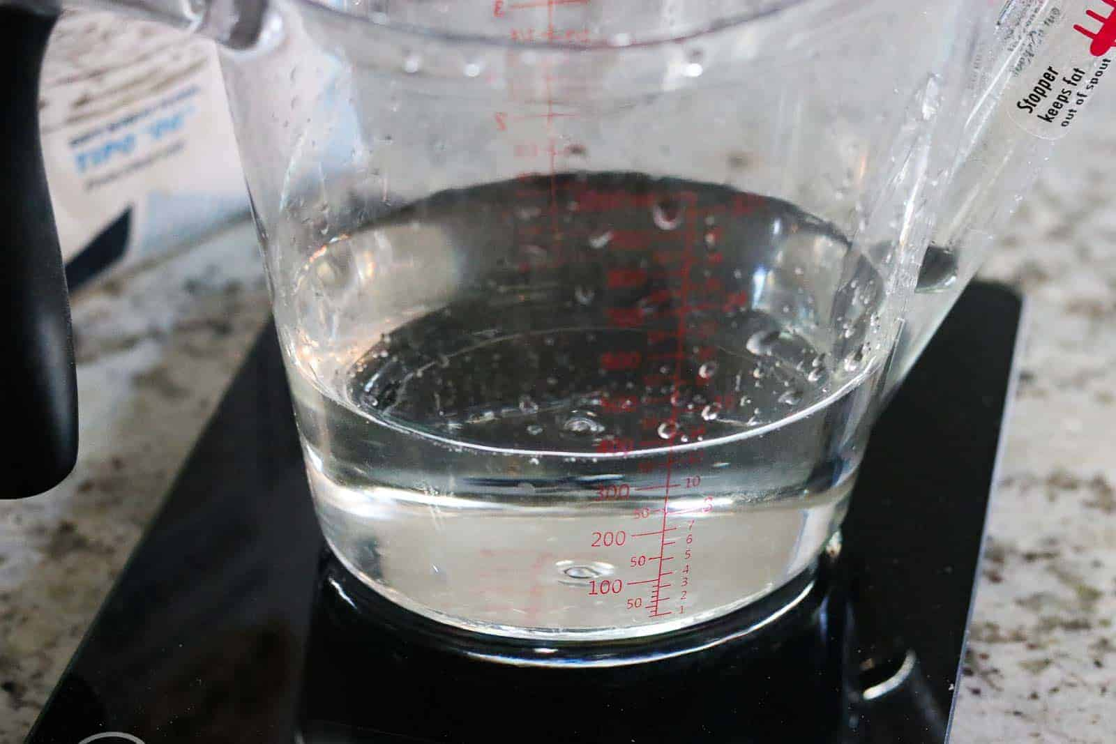 clear liquid measuring cup with water on a kitchen scale