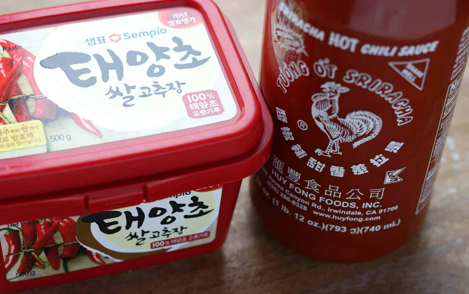Gochujang and Sriracha sauce in original containers on a wooden board from Gourmet Done Skinny