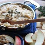 Caramelized Onion Kalua Pig Dip in a metal pan with slices of apples covered in dip on a blue plate on a wooden board from Gourmet Done Skinny