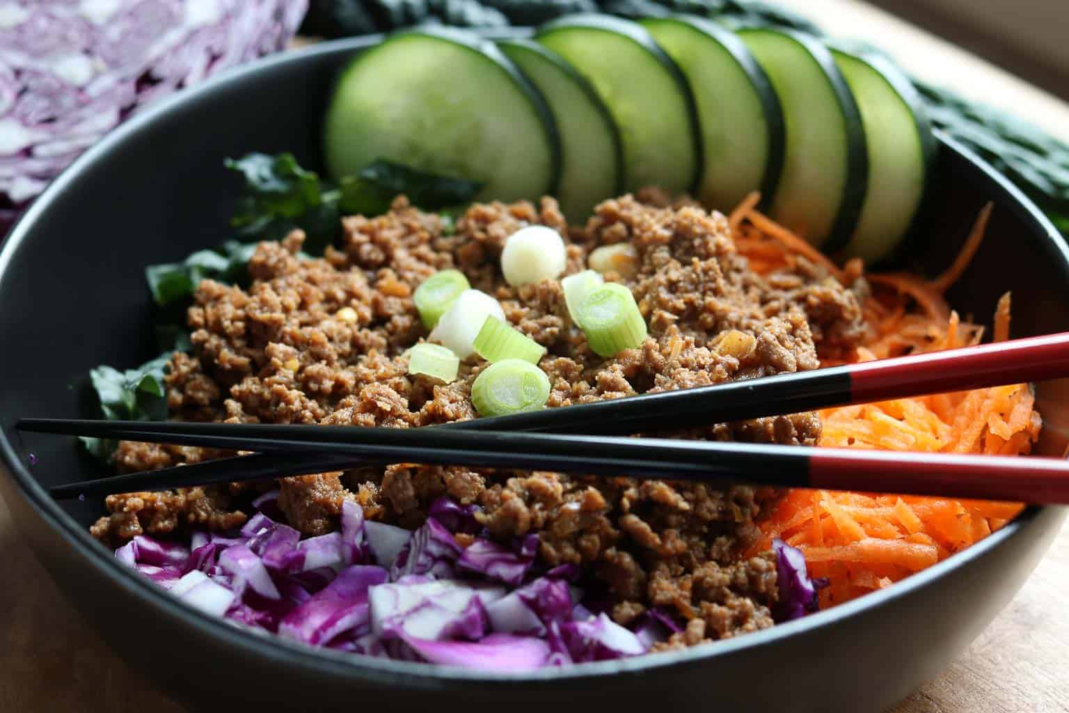 Healthy Instant Pot Korean Beef over kale, cabbage and shredded carrots in a black bowl with Healthy Instant Pot Korean Beef on top on a wooden board from Gourmet Done Skinny
