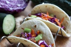 Quick, easy, healthy Korean Beef in the Instant Pot made into tacos on a taco rack with cucumber, red cabbage and ginger on a wooden board from Gourmet Done Skinny
