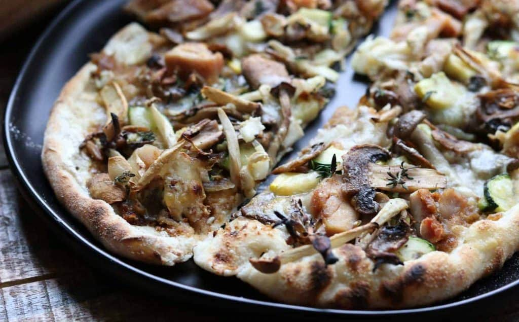 Wild Mushroom Pizza with Caramelized Onions, Garlic, Zucchini and Truffle Oil slices on a black plate from Gourmet Done Skinny