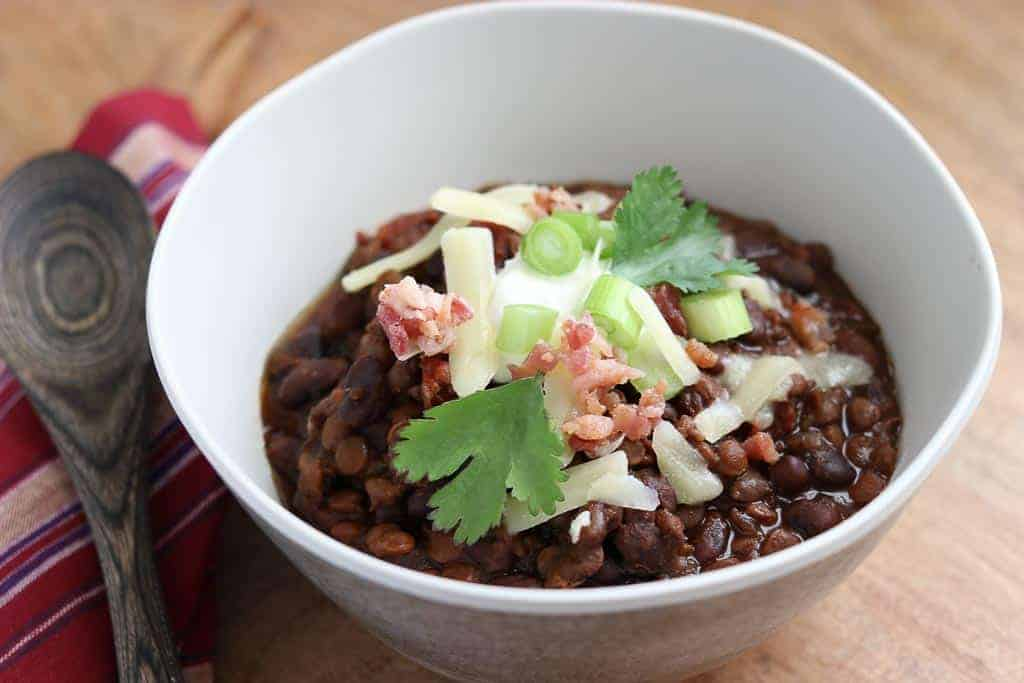 White bowl with Black Bean and Lentil Chili on a wooden board with wooden spoon and red and white napkin from Gourmet Done Skinny