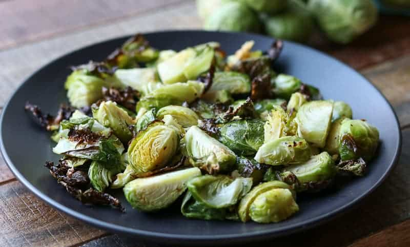 Air fried brussels sprouts on black plate on a wooden board from Gourmet Done Skinny
