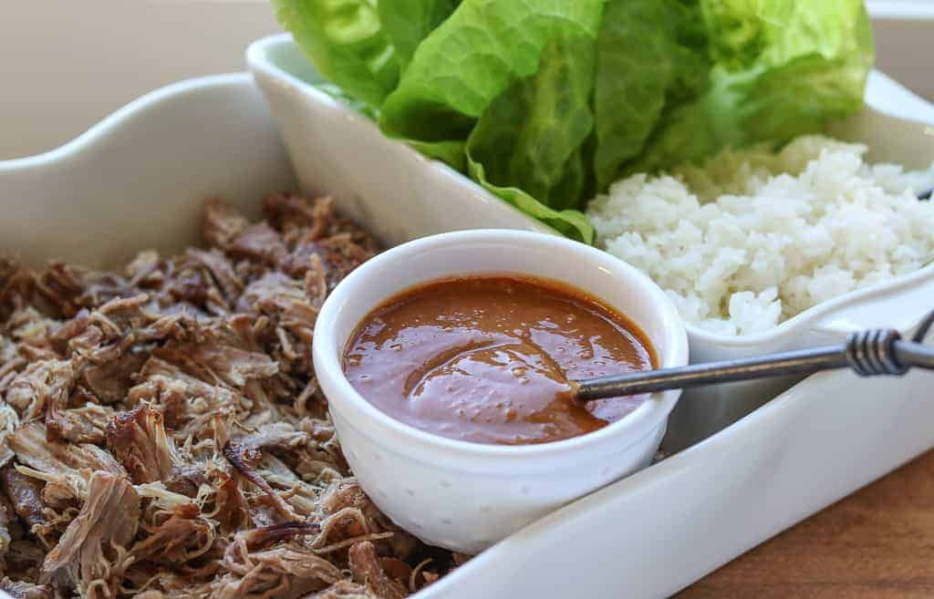 Kalua pork/kalua pig in a white dish with homemade hoisin sauce in a small white bowl with white rice and lettuce wraps on a wooden board from Gourmet Done Skinny