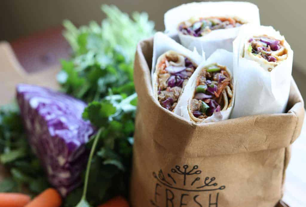 Thai wraps in a brown bag, with cilantro, cabbage and carrots in the background from Gourmet Done Skinny