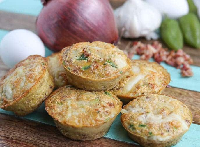 Delicious Chipotle Egg Cups ready to eat on a wooden board with red onion, egg, garlic, bacon and jalapeno in the background from Gourmet Done Skinny