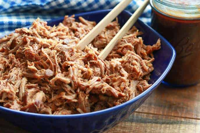 Easy healthy Instant Pot Pulled Pork in a blue bowl with a blue checked napkin and wooden tongs on a wooden board from Gourmet Done Skinny