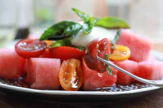 Tomatoes and watermelon pieces on plate with burrata, mint and basil shreddings, wine glasses blurred in background on a wooden board from Gourmet Done Skinny