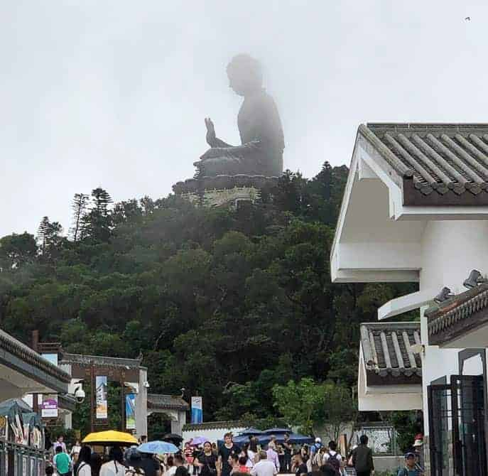 Big buddha on top of mountain with village down below