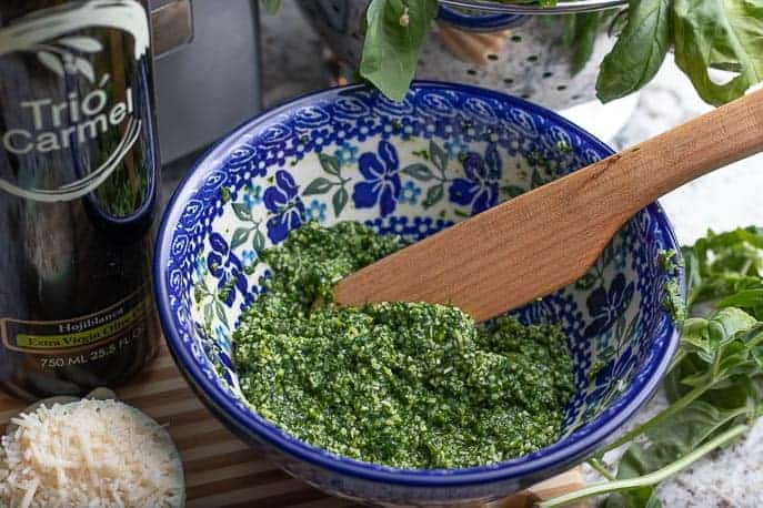 Homemade basil pesto in a Polish pottery bowl with a wooden spoon from Gourmet Done Skinny