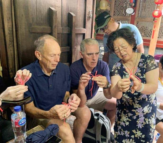 Tom and Pat learning to tie knots on the Hutong pedicab tour