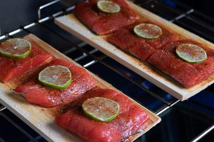 Cedar planks with salmon, chipotle seasoning and lime in the oven
