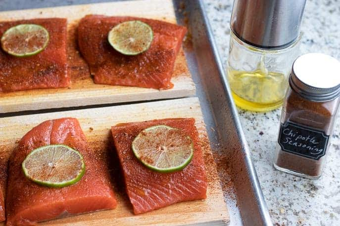 Salmon topped with Chipotle seasoning and lime on Cedar planks on a sheet pan with oil and seasoning from Gourmet Done Skinny