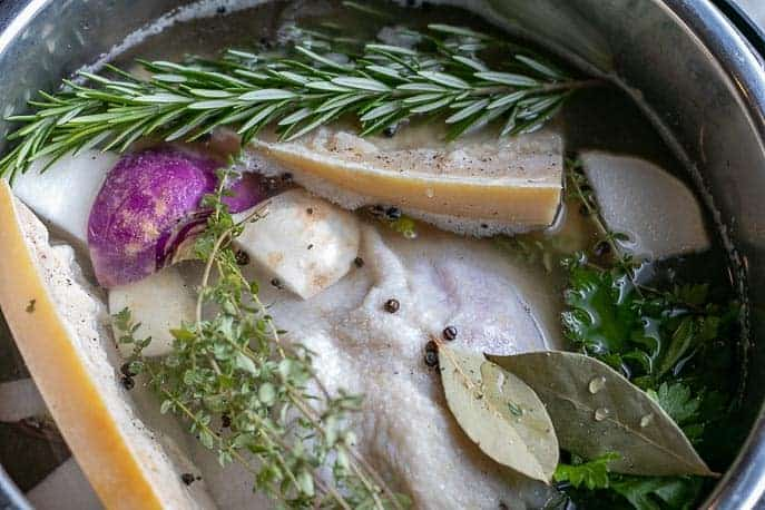 Whole chicken, parmesan rinds, rosemary, bay leaves, parsley in the Instant Pot from Gourmet Done Skinny