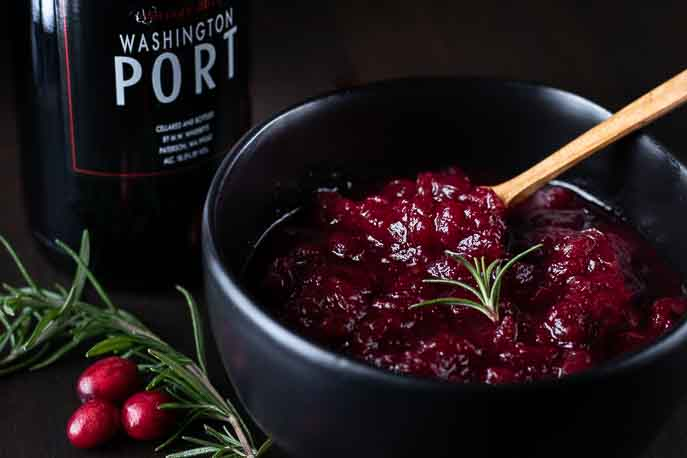 Cranberry sauce in a black bowl with a bottle of port, rosemary and cranberries from Gourmet Done Skinny