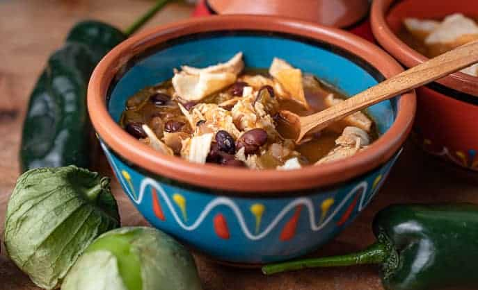 Mexican bowl with Chipotle Chicken Soup, wooden spoon, tomatillos and peppers