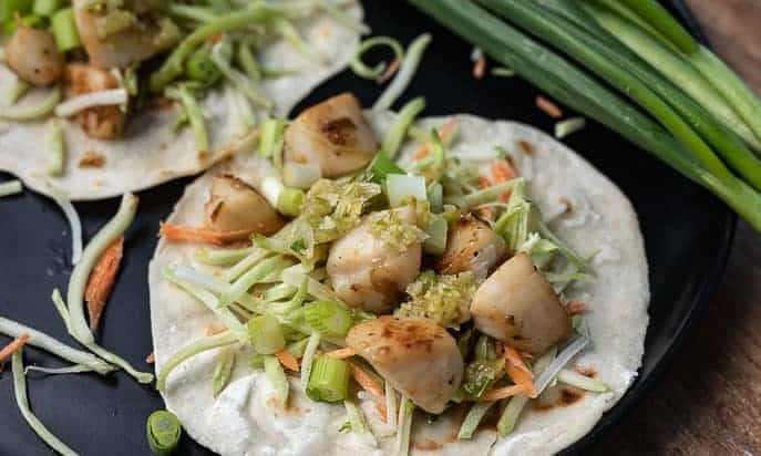 Pan Seared Scallop Tacos on a black plate with green onions in background
