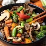 Clean Out Your Refrigerator Stir Fry in a black bowl on a wooden board with chop sticks and vegetables in the background
