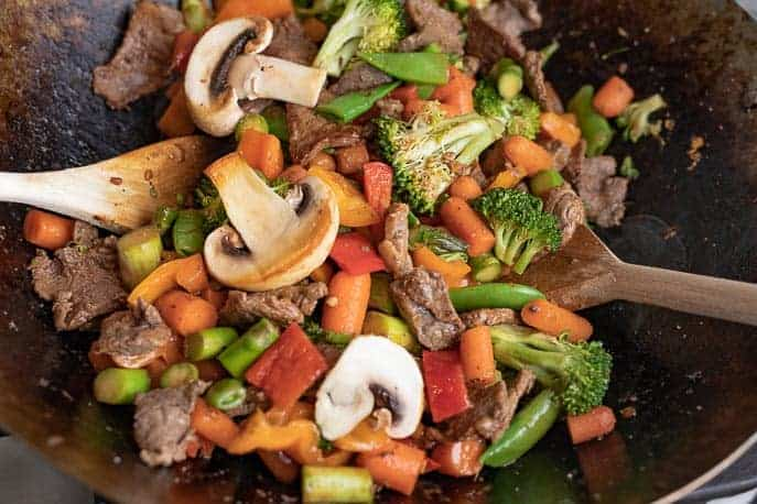 Clean Out Your Refrigerator Stir Fry in a wok with wooden spoons