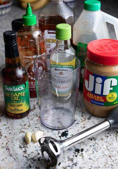 Ingredients for stir fry sauce and immersion blender on a marble counter top