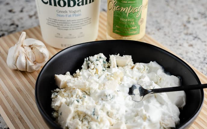 blue cheese and yogurt in a black bowl with garlic cloves, yogurt container and champagne vinegar on a wooden cutting board