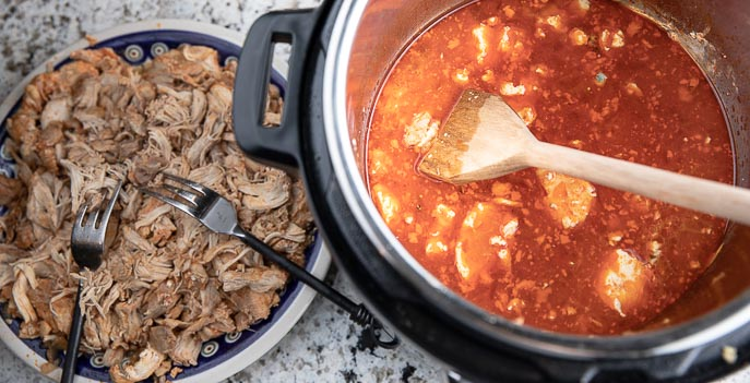 shredded chicken on a plate with fork, sauce in Instant Pot with wooden spoon
