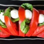 tomato sliced hasselback style on a black and white striped plate with basil, mozzarella and balsamic vinegar