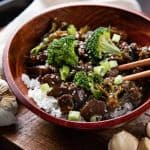 Mongolian beef and broccoli in a wooden bowl with rice and chopsticks on a wooden board with garlic cloves around