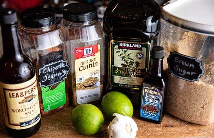 Ingredients for fajita marinade on a wooden board - worcestershire sauce, chipotle seasoning, cumin, oil, liquid smoke, brown sugar, 2 limes and head of garlic