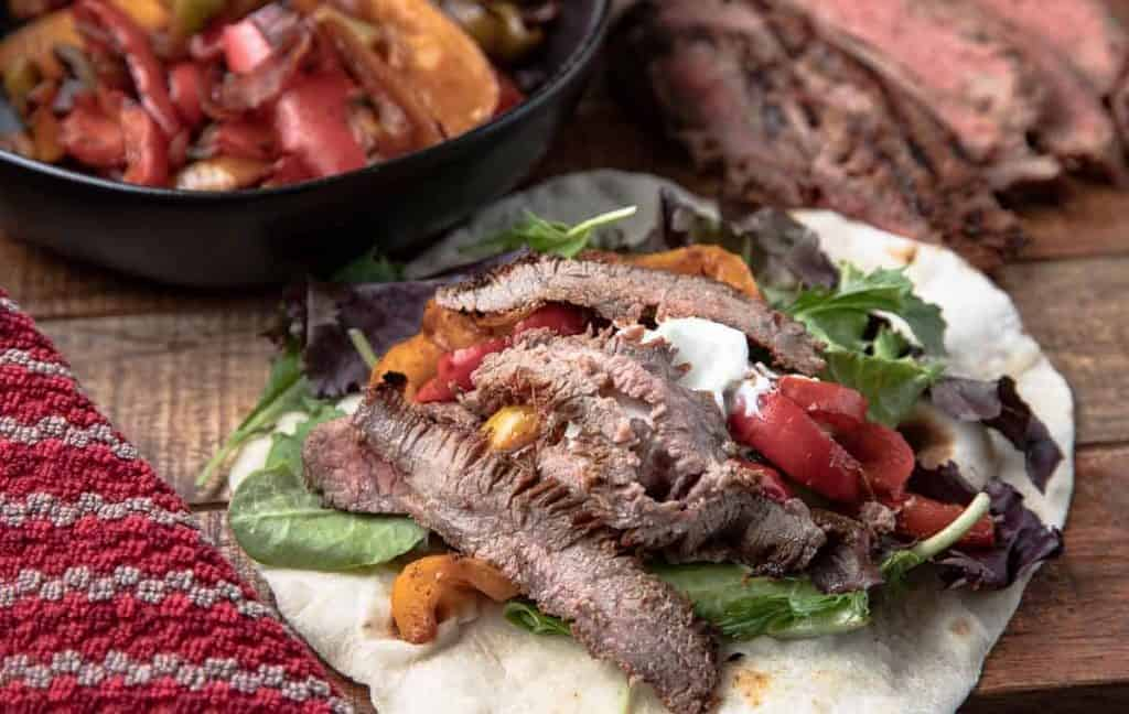 Grilled Steak on a tortilla with greens on a wooden board with vegetables and flank steak and napkin in the background